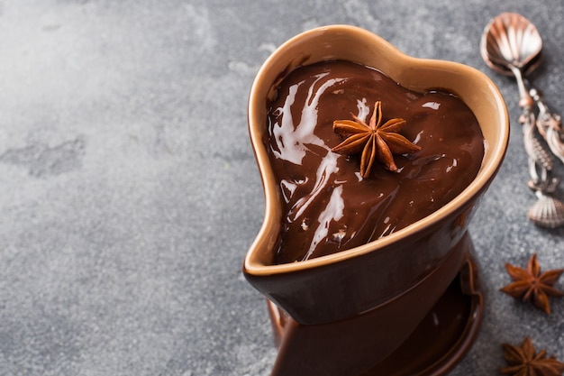 Шоколадная паста с корицей и анисом. фондю с шоколадом на темном бетонном столе. копировать пространство