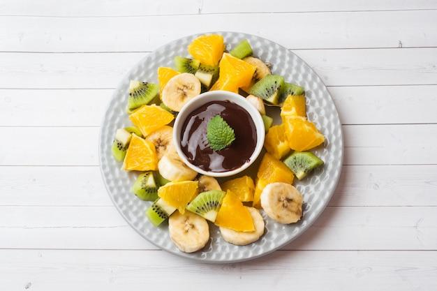 Шоколадное фондю с фруктами на белом столе. концепция летней вечеринки. копировать пространство