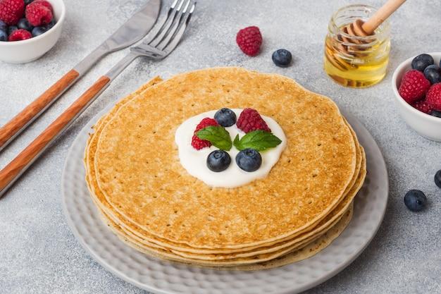 Тарелка вкусных тонких блинов с ягодами на сером столе копия пространство.
