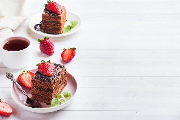 Трюфельный торт с шоколадом и клубникой и мятой на белом деревянном столе. выборочный фокус. копировать пространство