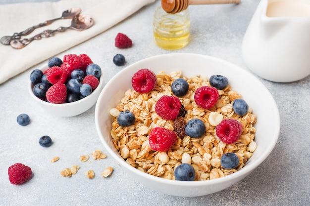 Здоровый завтрак. свежие мюсли, мюсли с йогуртом и ягоды на сером столе. копировать пространство