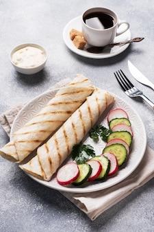 チーズとハーブを巻きます。フィリングとピタパンのグリル。きゅうり大根サラダ。健康的な朝食のコンセプトです。一杯のコーヒー。