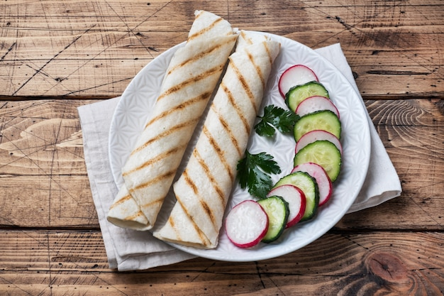 チーズとハーブを巻きます。フィリングとピタパンのグリル。きゅうり大根サラダ。健康的な朝食のコンセプトです。