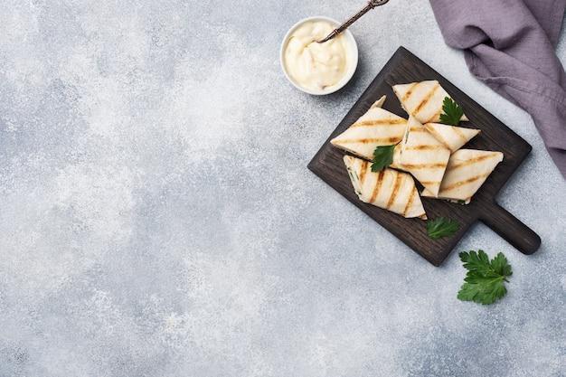 チーズとハーブを巻きます。フィリングとピタパンのグリル。きゅうり大根サラダ。健康的な朝食のコンセプトです。コピースペース