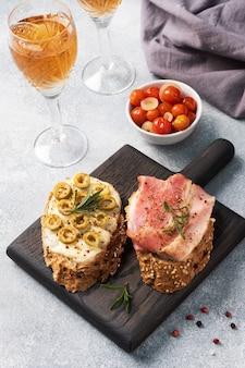 木製のまな板にクリームチーズ、ベーコン、オリーブと全粒パンのサンドイッチ。白ワインのグラス。灰色のコンクリートテーブル。