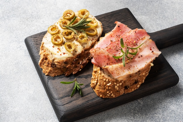 木製のまな板にクリームチーズ、ベーコン、オリーブと全粒パンのサンドイッチ。白ワインのグラス。コピースペースを持つ灰色のコンクリートテーブル。