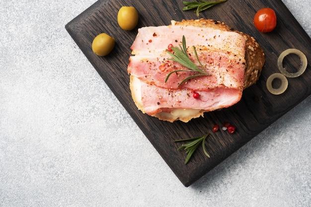 全粒パンサンドイッチ、クリームチーズ、木製のまな板にベーコン。灰色のコンクリートテーブルコピースペース。