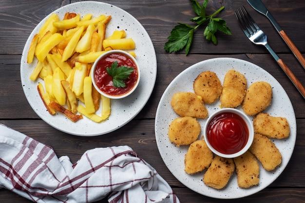 Жареный картофель и куриные наггетсы с соусом из томатного кетчупа. концепция быстрого питания нездоровой пищи.