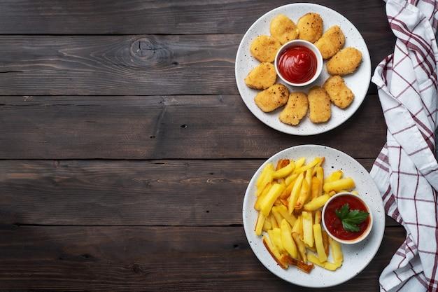 Жареный картофель и куриные наггетсы с соусом из томатного кетчупа. концепция быстрого питания нездоровой пищи. деревянный стол. копировать пространство