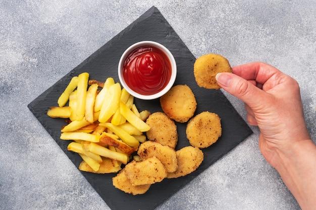 Жареный картофель и куриные наггетсы с соусом из томатного кетчупа. концепция быстрого питания нездоровой пищи. серый бетонный стол копирование пространства.