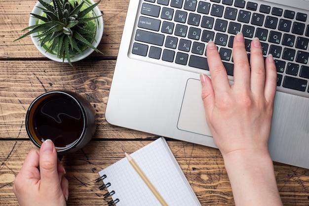 自宅やオフィスで働く木製のテーブル。コンピューターのラップトップのコーヒーサボテン。フラット横たわっていた概念コンピューターの手で働く女性。