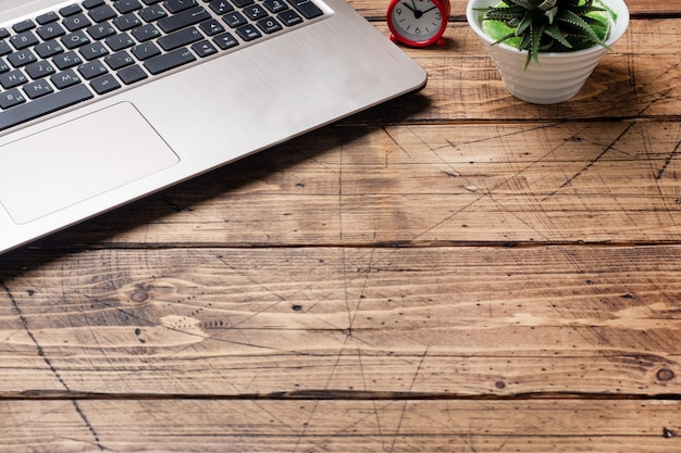 自宅やオフィスで働く木製のテーブル。コンピューターのラップトップのコーヒーサボテン。フラットレイアウトの概念コピースペース。