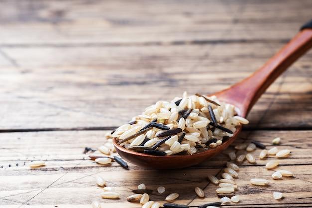 Сырцовый дикий рис в деревянной ложке. сырцовые рисовые крупы на деревянном столе. копировать пространство