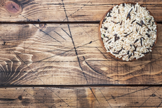 Сырцовый дикий рис в деревянном шаре. сырцовые рисовые крупы на деревянном столе. копировать пространство