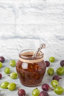 灰色のテーブルに新鮮なスグリの果実が付いている瓶のスグリのジャム。スペースをコピーします。