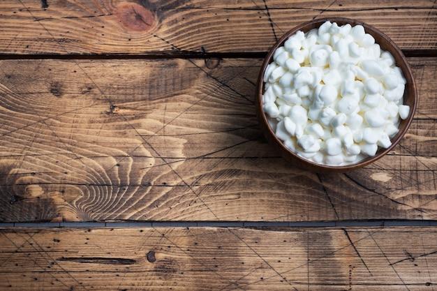 木製のボウルに新鮮なカッテージチーズの穀物。クリーム入りの顆粒の凝乳。木製の素朴な背景。 。