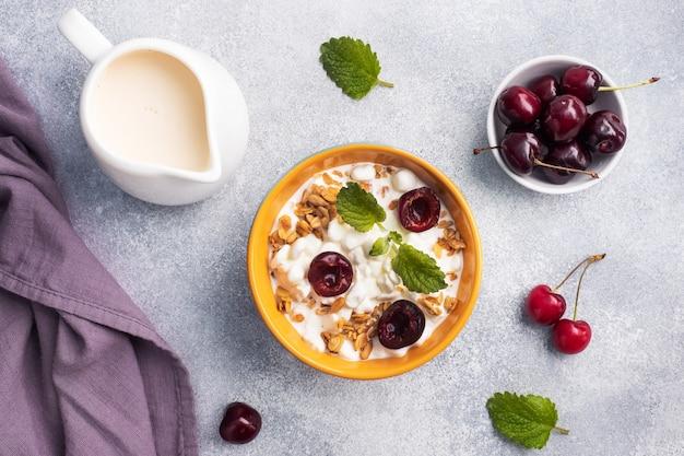 プレート上の新鮮なチェリーと穀物カードミューズリー。カッテージチーズとベリーのコンセプト健康的な朝食。