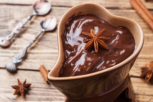 Шоколадная паста с корицей и анисом. фондю с шоколадом на деревянном столе. копировать пространство