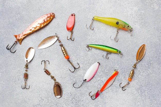 コピースペース付きの灰色のテーブルでさまざまな魚を捕まえるためのセットの釣りフックと餌。フラットレイ