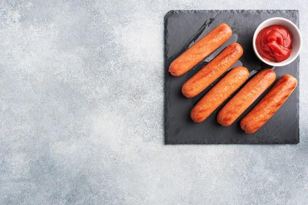 ジューシーな焼き肉ソーセージとトマトソースとケチャップとコンクリートのスタンド。脂肪の多いファーストフード。コンセプトの不健康な食事。コピースペース