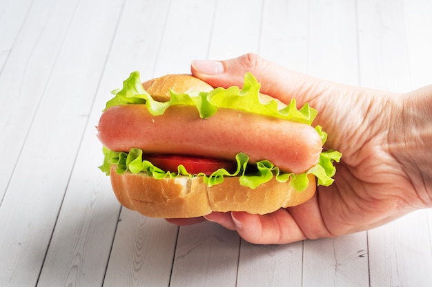 Хот-дог с салатом помидор и колбаса держать в руках.