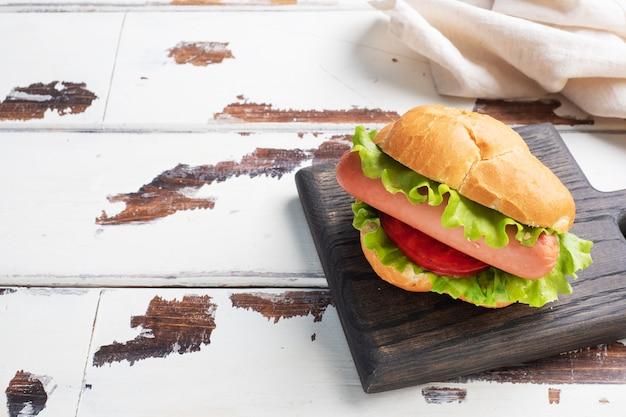 木の板のホットドッグ。レタストマトとソーセージのホットドッグ。コピースペース。