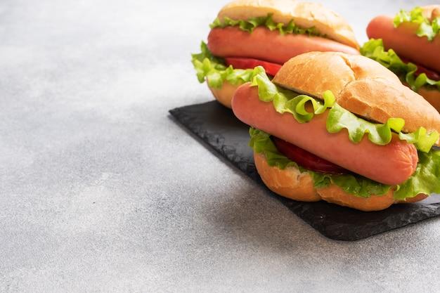 コンクリートの灰色の背景上のホットドッグ。レタストマトとソーセージのホットドッグ。コピースペース。