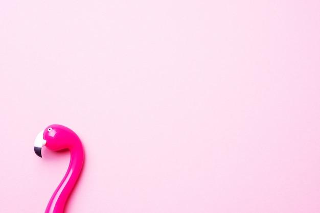 ピンクの背景にピンクのペンフラミンゴ。コピースペースフラットレイアウト。