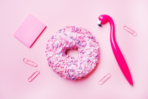 ピンクの背景にピンクのドーナツとフラミンゴのペン。トップビューフラット横たわっていた。