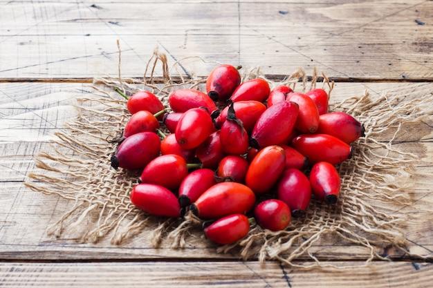 木製の背景に赤い果実ローズヒップフルーツ。コピースペース。