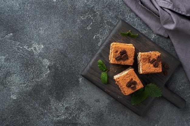 繊細なクリーム、コーヒー豆、ミントの葉が入ったティラミスケーキ。コピースペースと暗いコンクリートの背景。上面図。