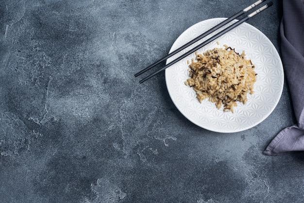 箸で皿に玄米と皮をむいたご飯。