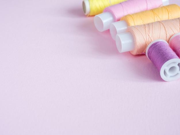 カラフルな縫製ボタンとピンクの背景のスレッド