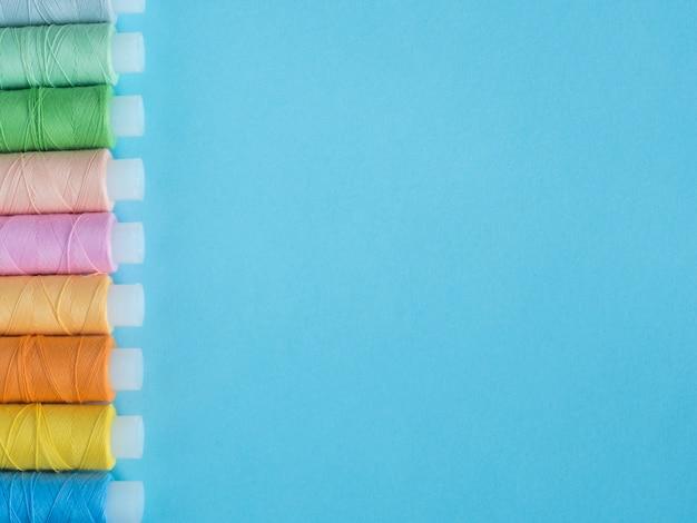 コピースペースフラットクラッチで青い背景に色とりどりの縫製ボタン。