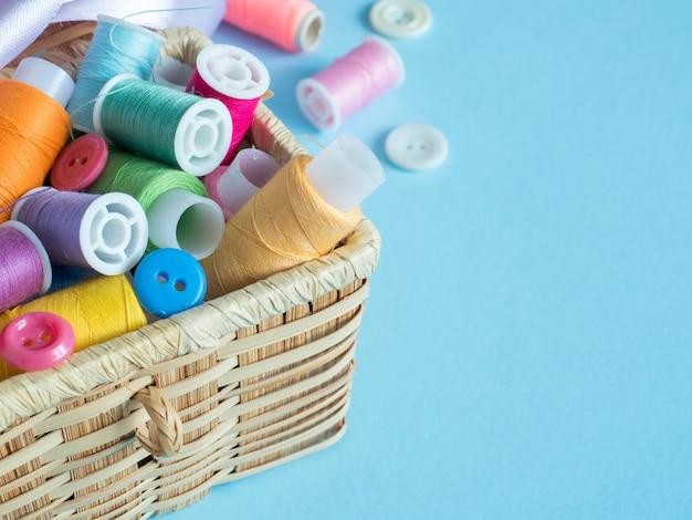 カラフルな縫製ボタンと青色の背景に木製の箱の糸
