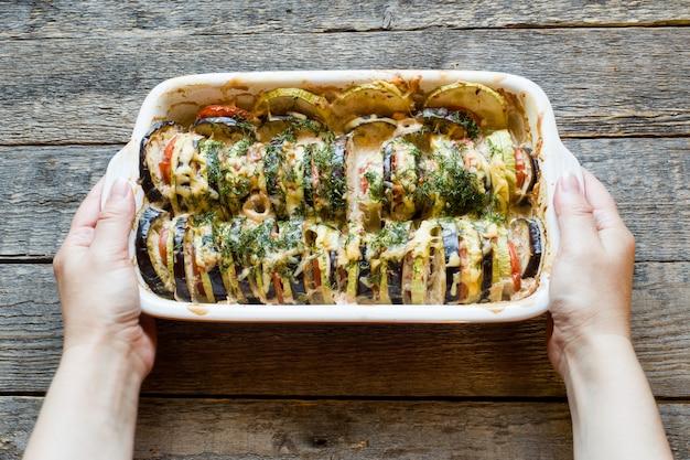 焼き野菜ズッキーニ茄子のトマト素朴な木製の背景にラタトゥイユの一種