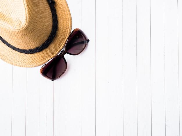 Летний фон соломенная шляпа браслеты сандалии солнцезащитные очки ракушки на синем столе