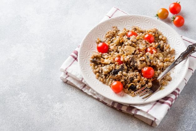 きのこと皿の上のチェリートマトのそば米雑炊。コピースペース