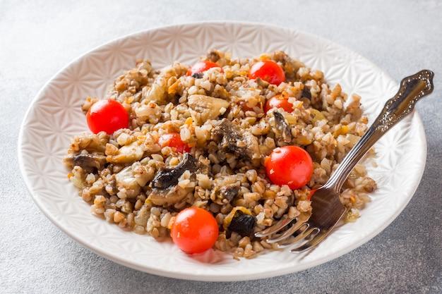 きのこと皿の上のチェリートマトのそば米雑炊。