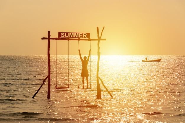 夏のサインと海の上をスイング遊んで幸せな人々のシルエット。