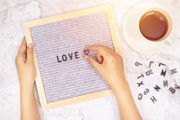 白い大理石の机の上のハートマークを持っている女性の手でレターボードに愛という言葉