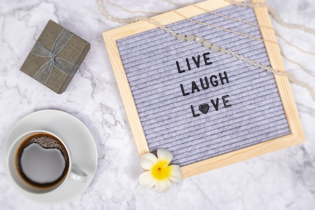 Слово живой смех любовь на доске объявлений на белом мраморном столе с чашкой кофе и подарочной коробке