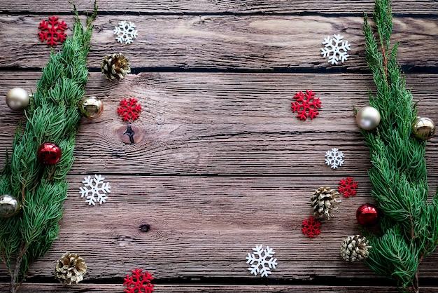 Зеленая сосна, золотая шишка, снежинки, елочные украшения шар на деревянном фоне с копией пространства