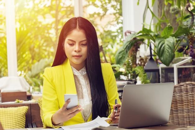 自信を持ってアジアビジネス女性のラップトップと電話での作業