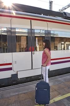 スーツケースで電車を待っている女性