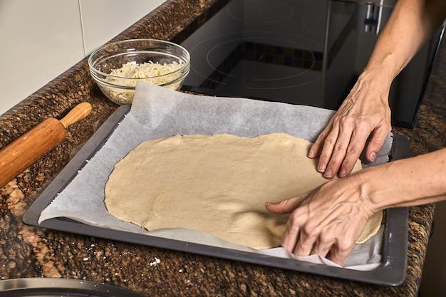 Руки женщины работают над тестом для пиццы
