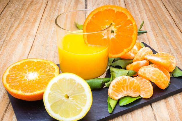 いくつかの成熟した柑橘類と黒板の木製テーブルの上のジュースのガラス