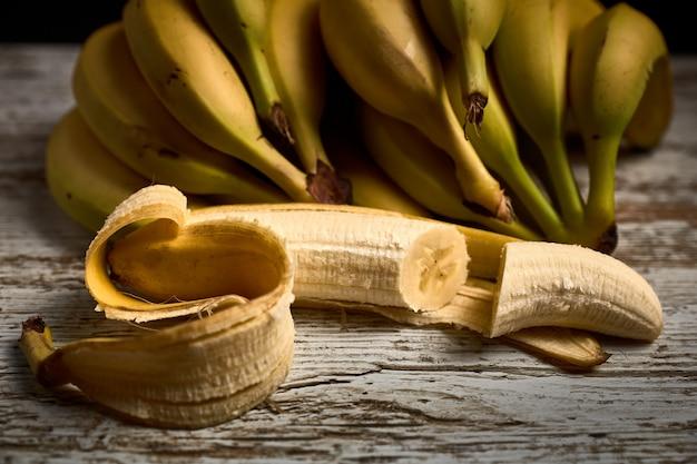 Букет из вкусных спелых желтых бананов на светлой деревянной доске