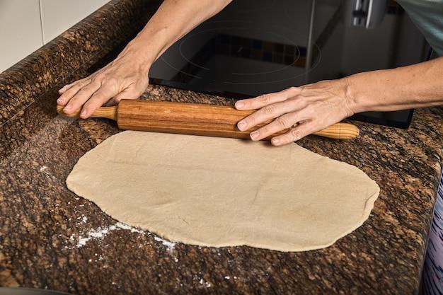 おいしいピザを調理する生地に取り組んでいる女性の手