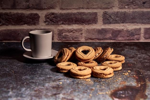ホットミルクの豊富なカップの横にある甘いクッキーのおいしい束